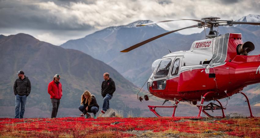 Helicopter landing on scenic ridge near Denali National Park.
