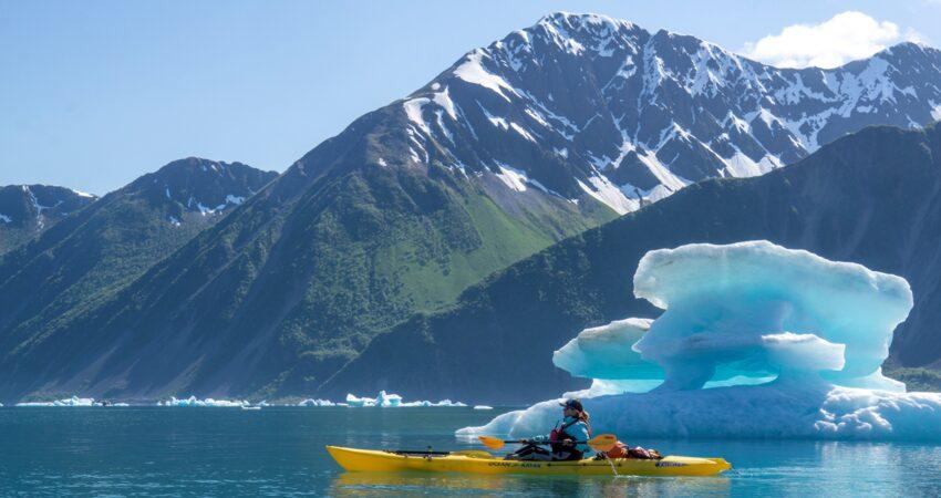 Kayaker among Bear Glacier icebergs.